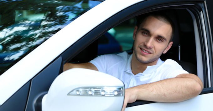 Young man behind the wheel of his car